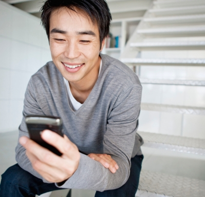 Man sitting on stairs using cell phone