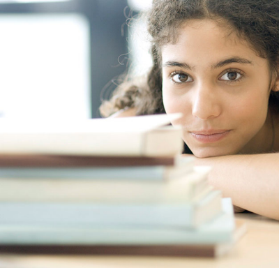 Young woman looking over stack of books at camera