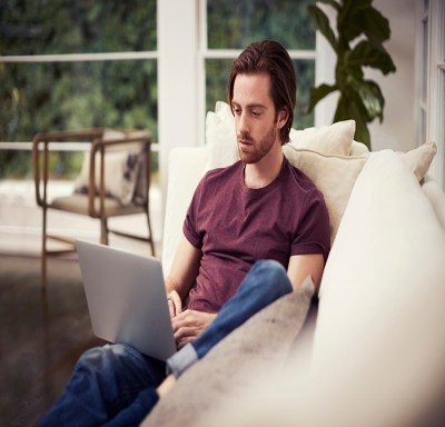 young man on couch with laptop